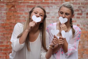Girls holding hearts in front of mouths